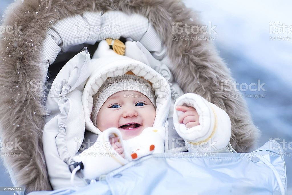 Baby in stroller in a winter park stock photo