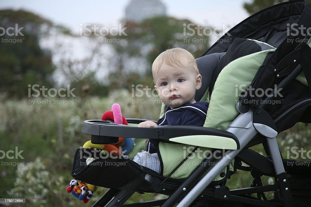 Baby in stroller outside in park looking at camera stock photo