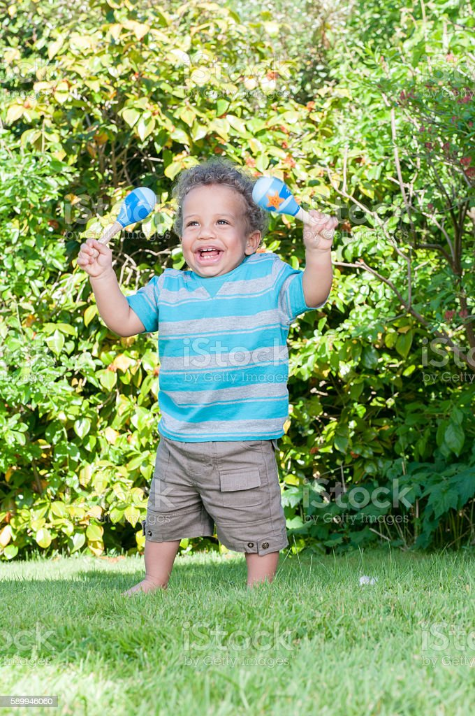 Baby In The Garden/ Park holding Rattles stock photo