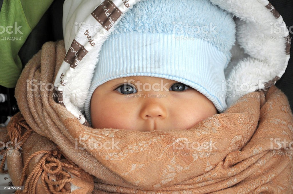 Baby in warm clothes in cold weather stock photo