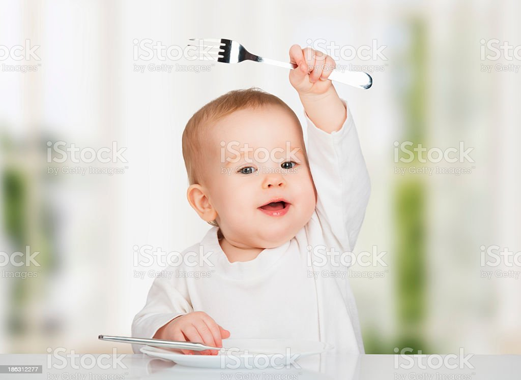 Baby in white clothes, waving his cutlery in the air royalty-free stock photo