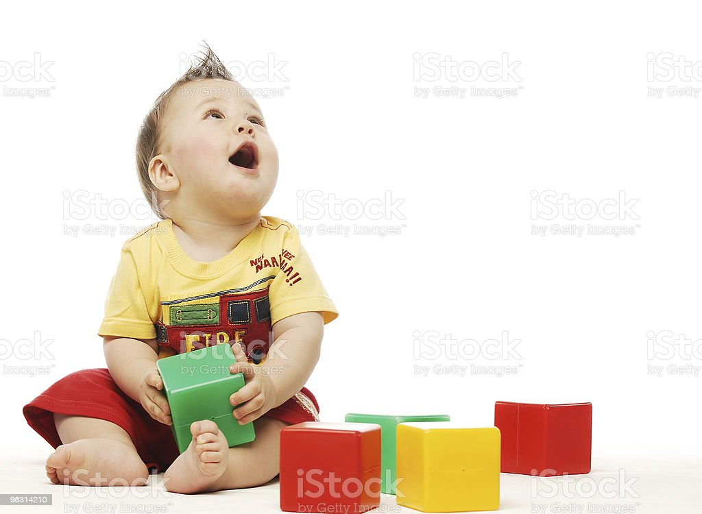 Baby in yellow shirt playing with blocks looking up surprised stock photo