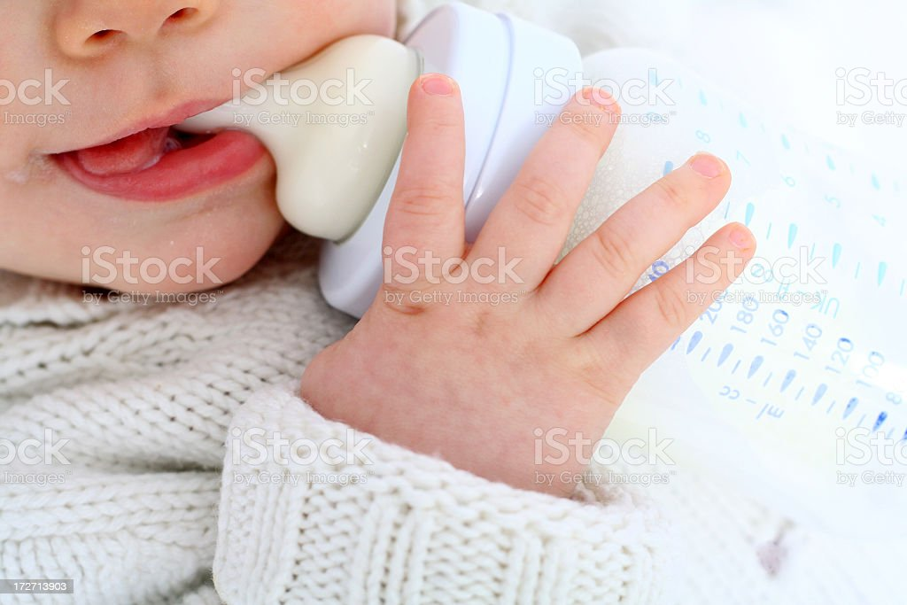 Baby is drinking milk out of a bottle stock photo