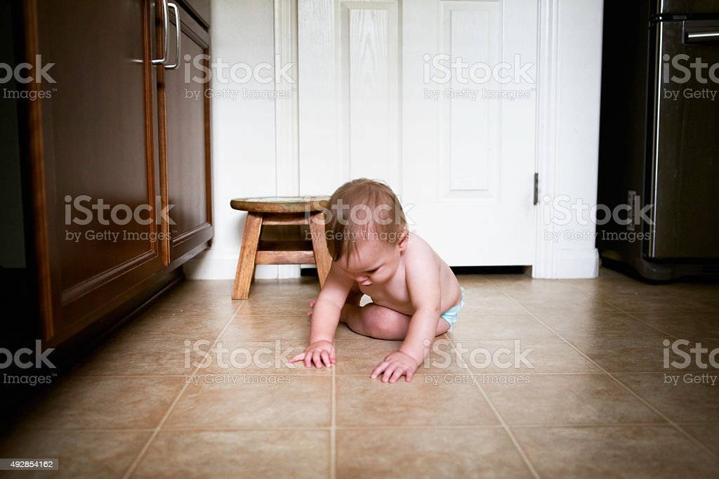 Baby is Grasping Tiny Crumbs in Kitchen stock photo