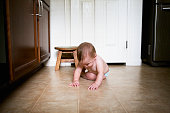 Baby is Grasping Tiny Crumbs in Kitchen