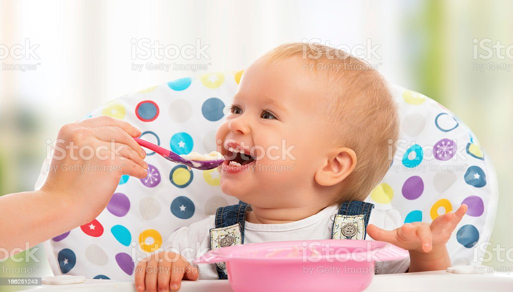 happy mother feeds funny  baby from  spoon stock photo