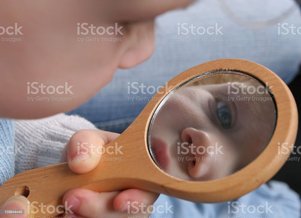 A baby is looking at its reflection in a hand mirror  royalty-free stock photo