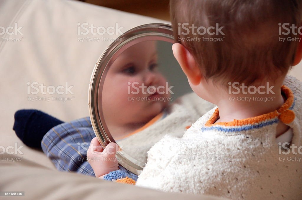 Baby is playing with a mirror royalty-free stock photo