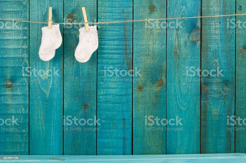 baby knitted woolen socks on primako on turquoise wooden background stock photo