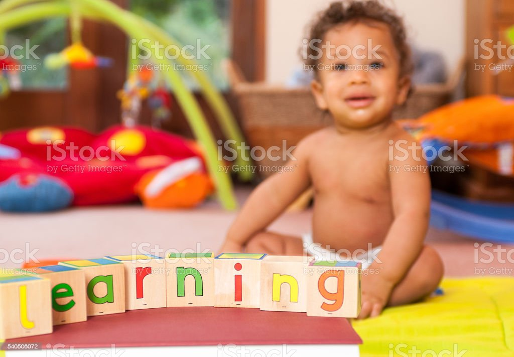 Baby learning though play - using abc blocks stock photo