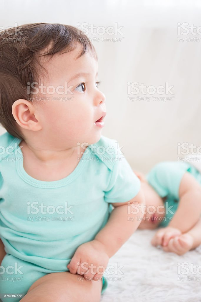 baby look somewhere on bed stock photo