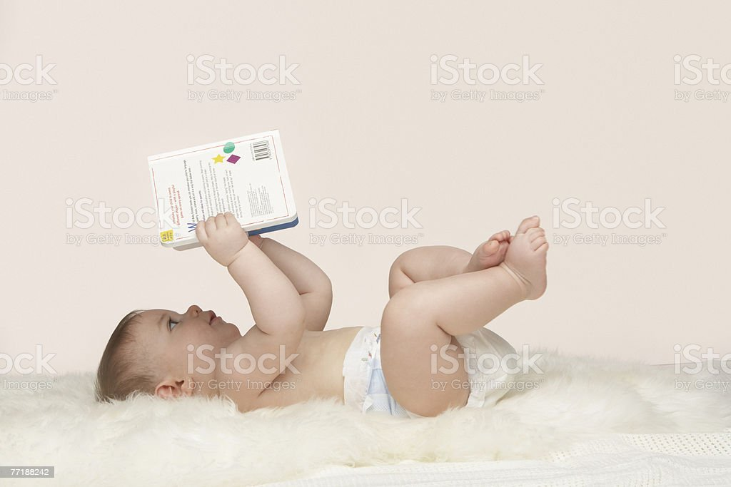 A baby looking at a book royalty-free stock photo