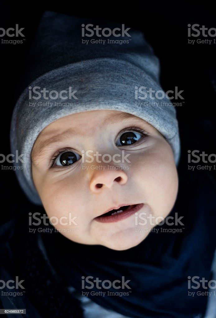 Baby looking at camera with surprised expression, portrait. stock photo