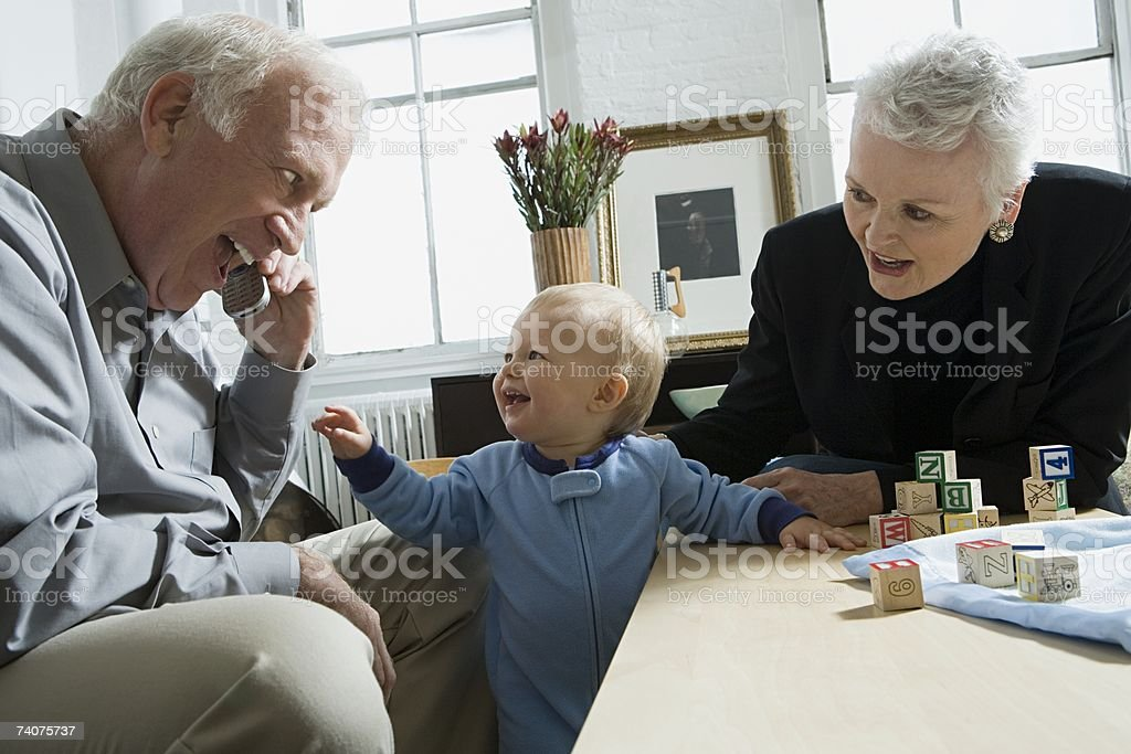 Baby looking at grandfather with cellphone stock photo