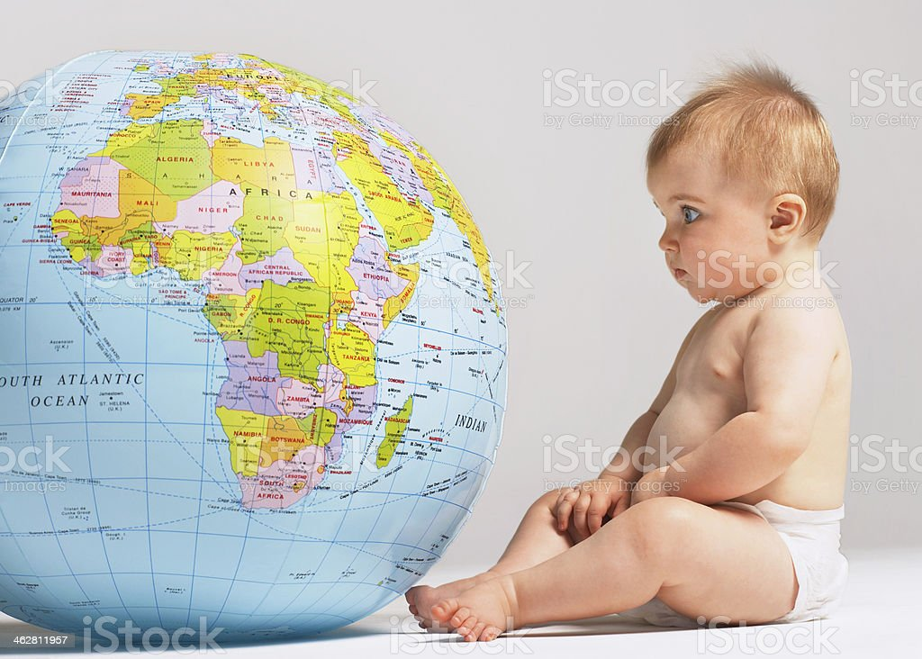 Baby Looking At Inflatable Globe stock photo