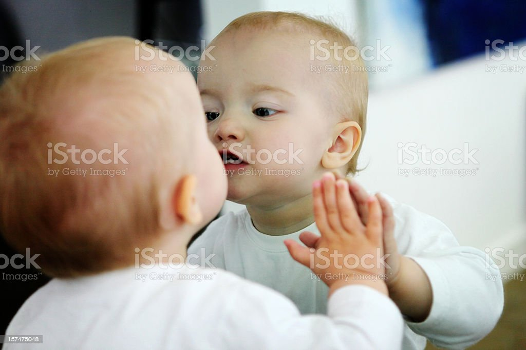 Baby looking at itself in a mirror stock photo