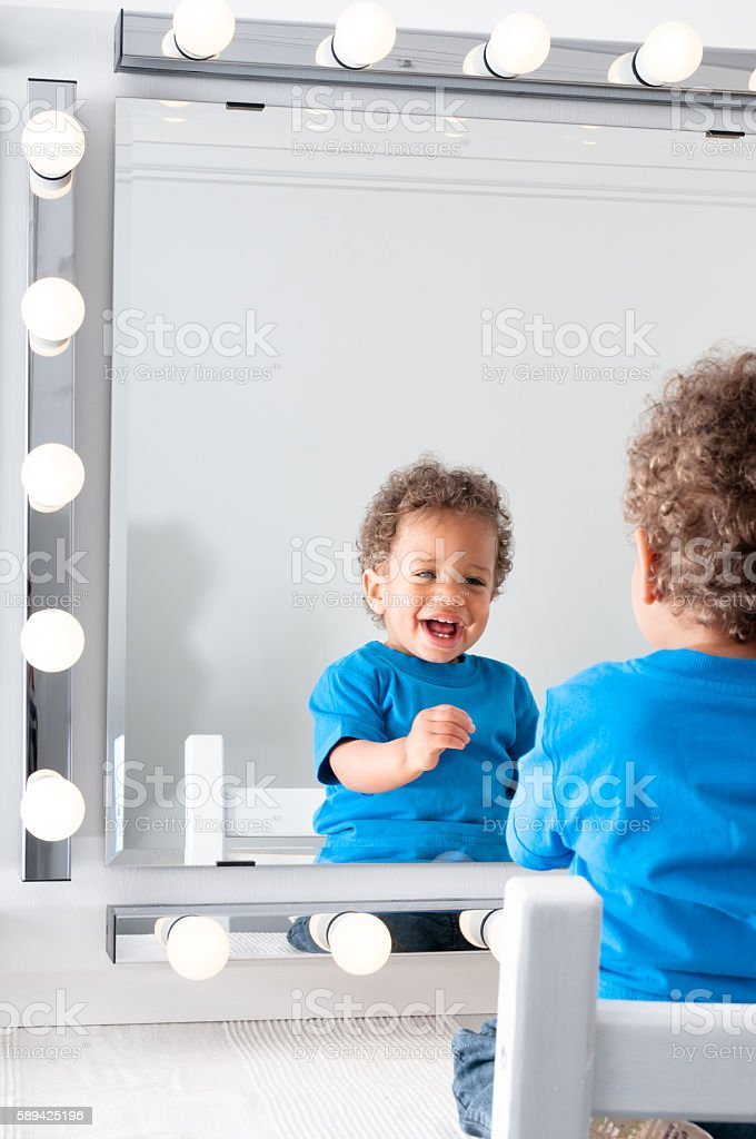 Baby Looking In The Mirror Smiling stock photo