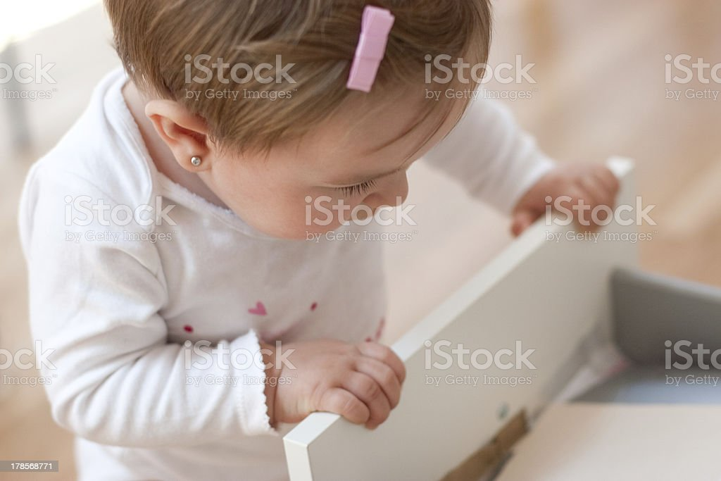 Baby looking inside a drawer stock photo