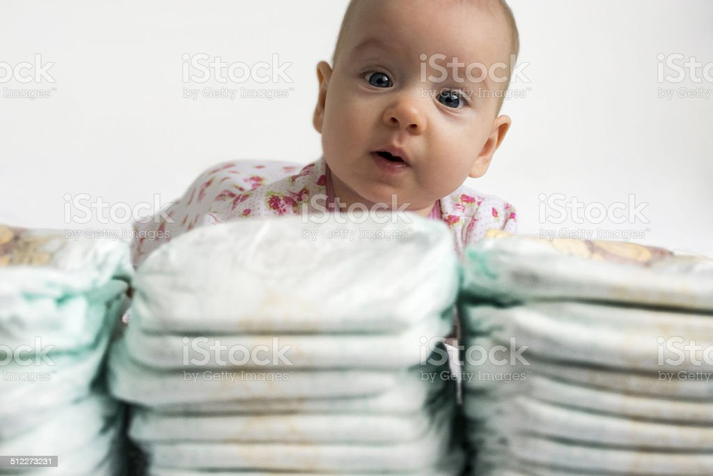 baby looking over a stack of diapers stock photo