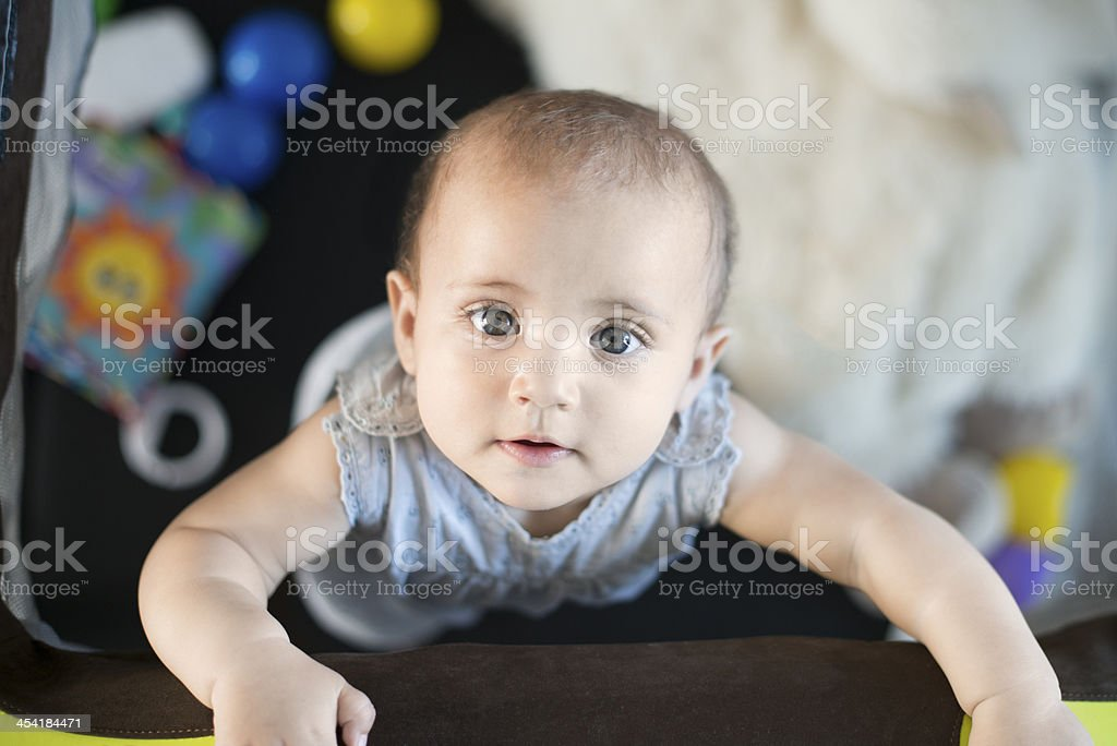 Baby looking up from play pen stock photo