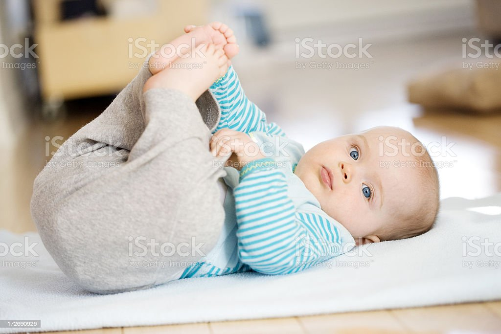 Baby lying down grabbing feet stock photo
