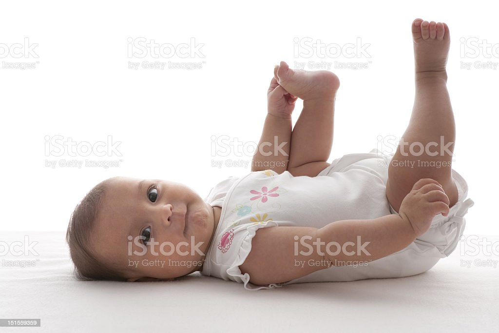 Baby lying on her back holding one foot stock photo