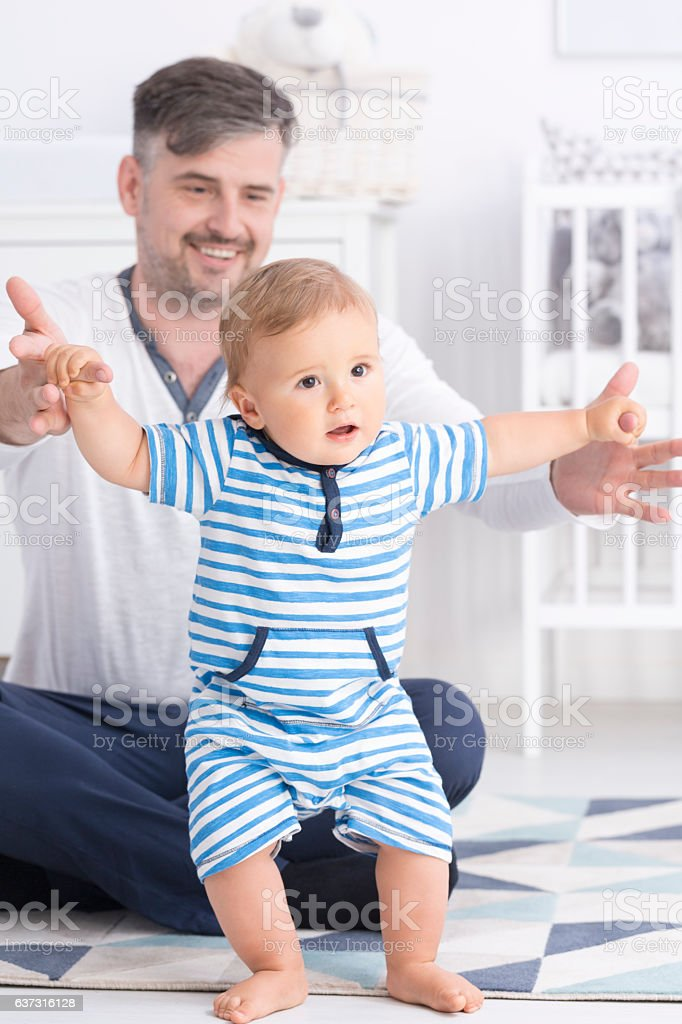 Baby making first steps with father stock photo