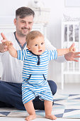 Baby making first steps with father