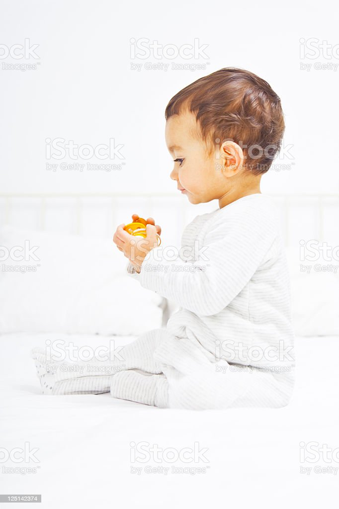 Baby on bed playing with pacifier royalty-free stock photo