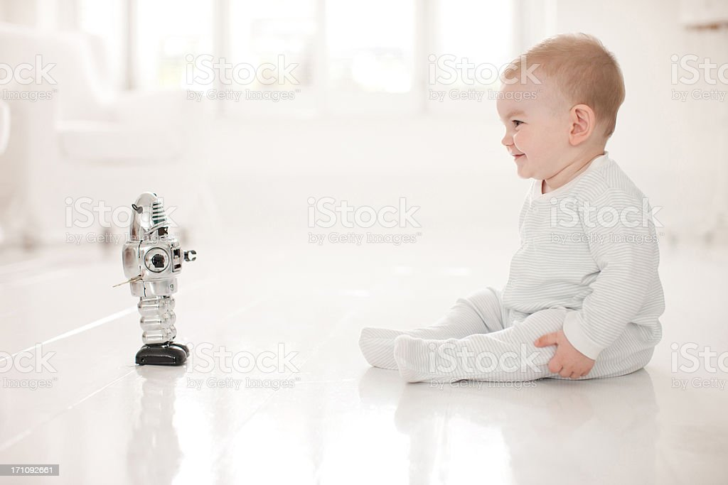 Baby on floor looking at toy robot stock photo