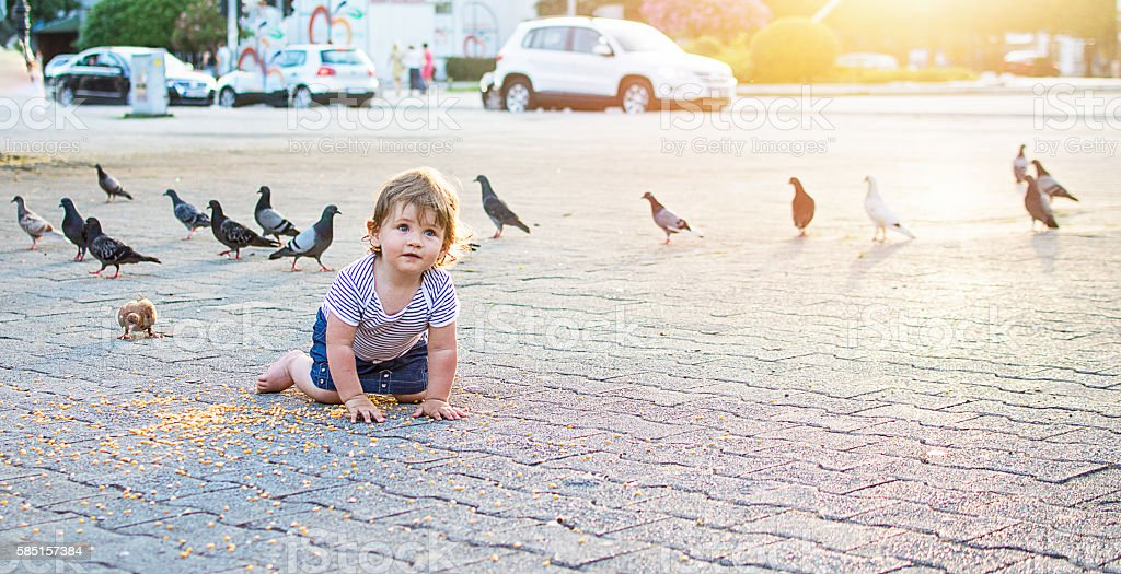 Baby on town square feeding pigeons stock photo