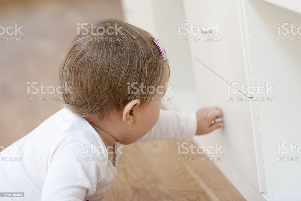 Baby opening a drawer stock photo
