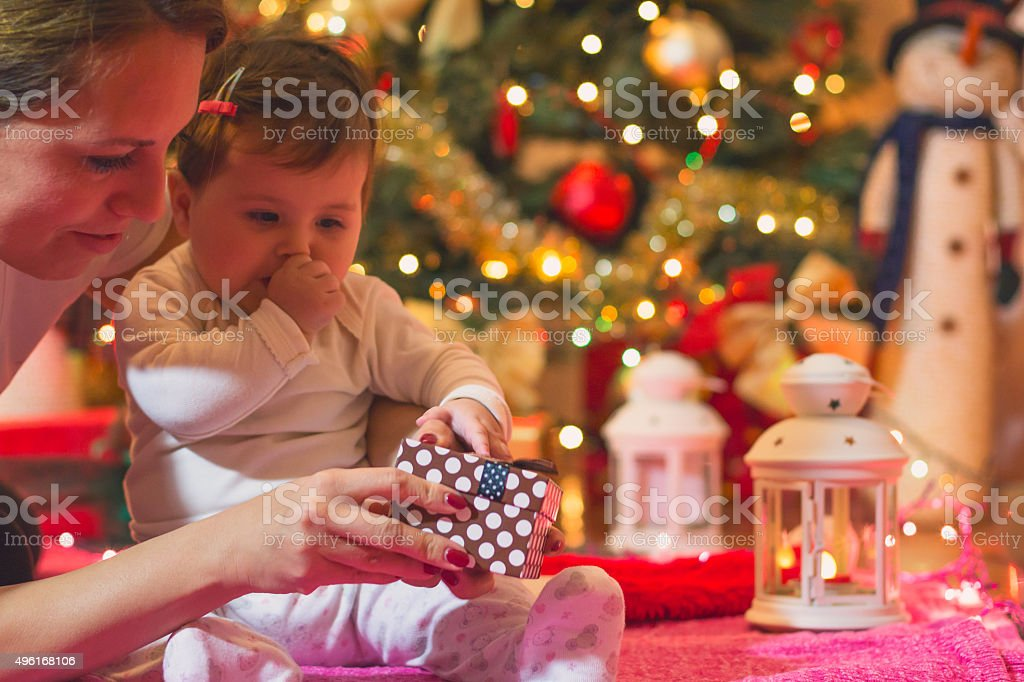 baby opens its first New Year's gift with her mother stock photo