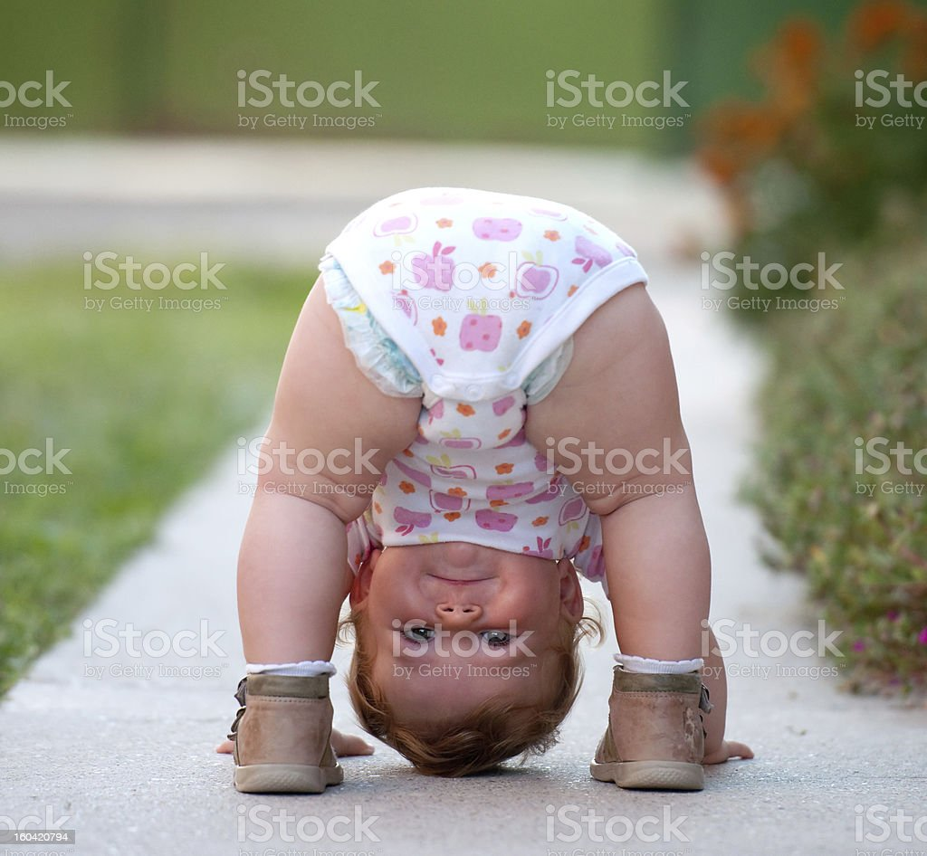 A baby outside with her butt in the air stock photo