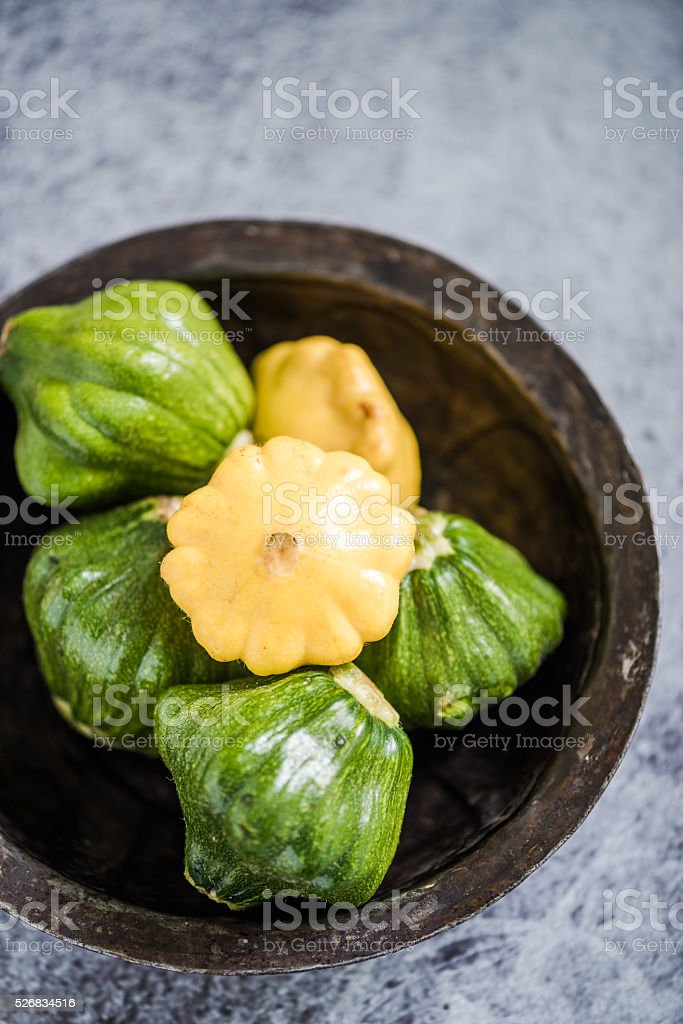 Baby pattypan in rustic bowl stock photo