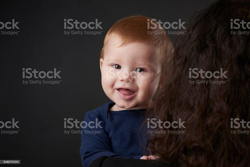 Baby peeking over mothers shoulder stock photo