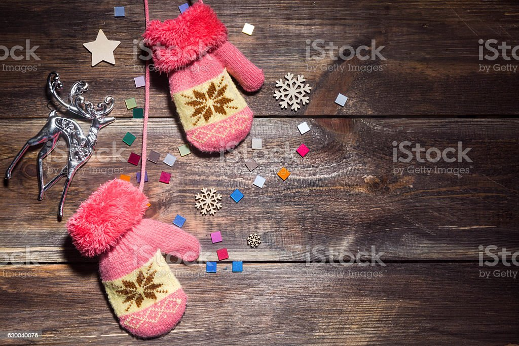 baby pink knitted mittens on a brown wooden Board stock photo