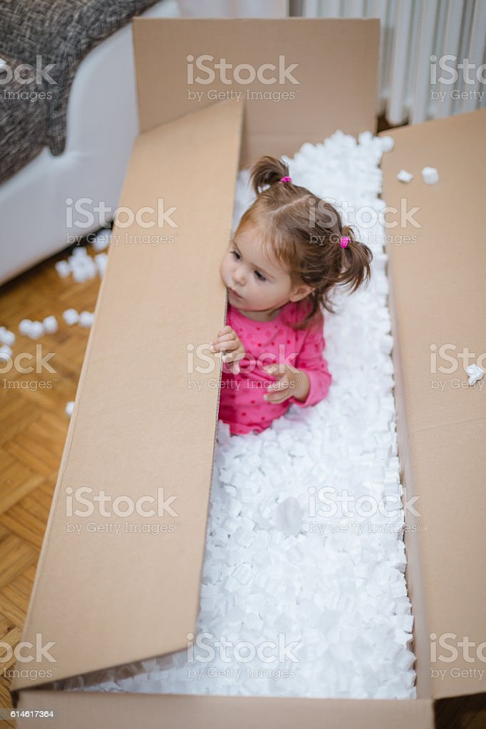 baby playing and hiding in a cardboard box stock photo
