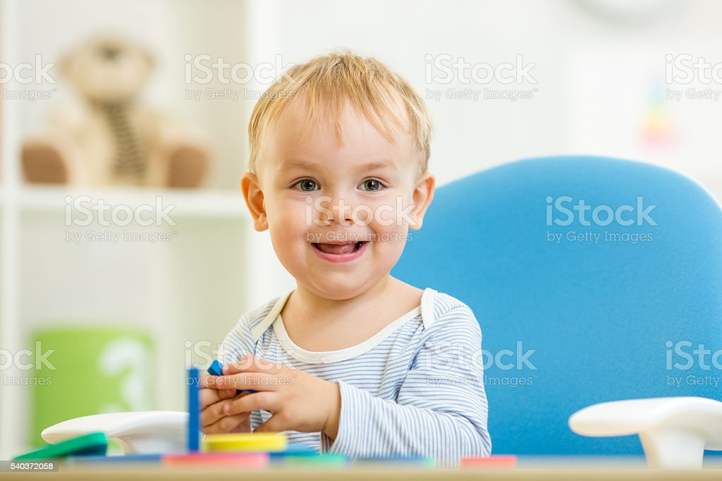 Baby playing education toy at table in nursery stock photo