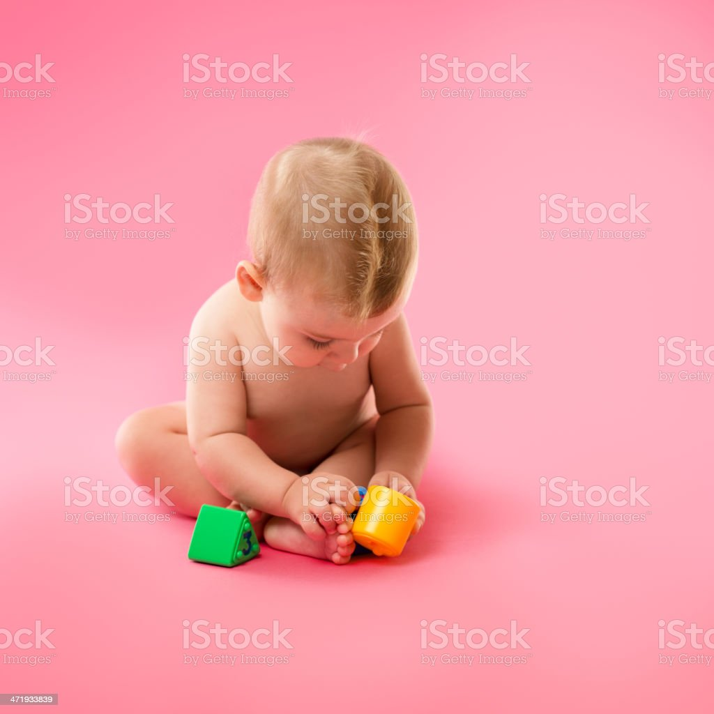 Baby playing on pink background royalty-free stock photo