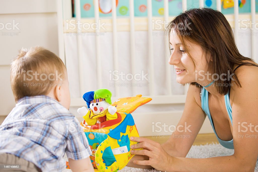Baby playing with a Jack-in-the-Box with his mother stock photo