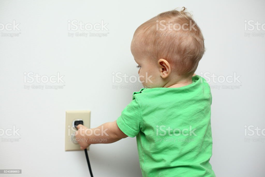 Baby playing with a power cord stock photo