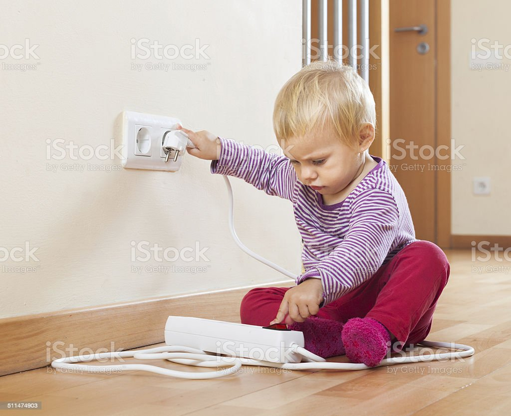 Baby playing with electrical extension stock photo