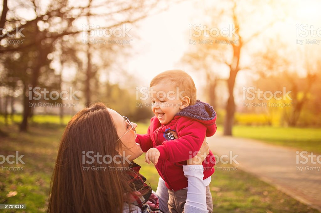 Baby playing with mother stock photo