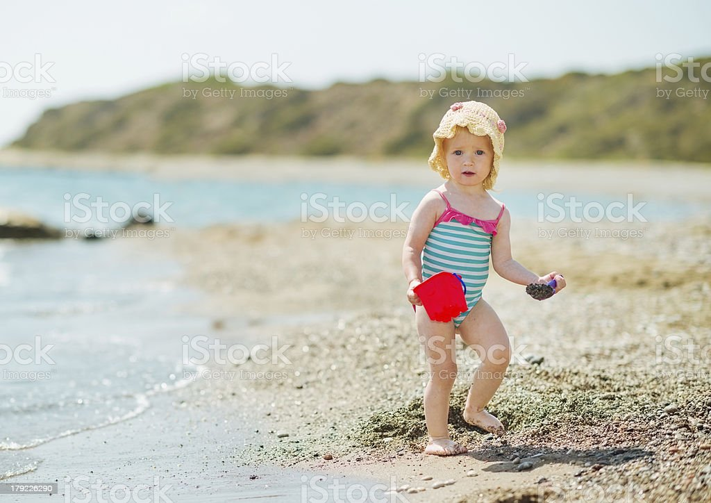 Baby playing with pail on sea shore royalty-free stock photo