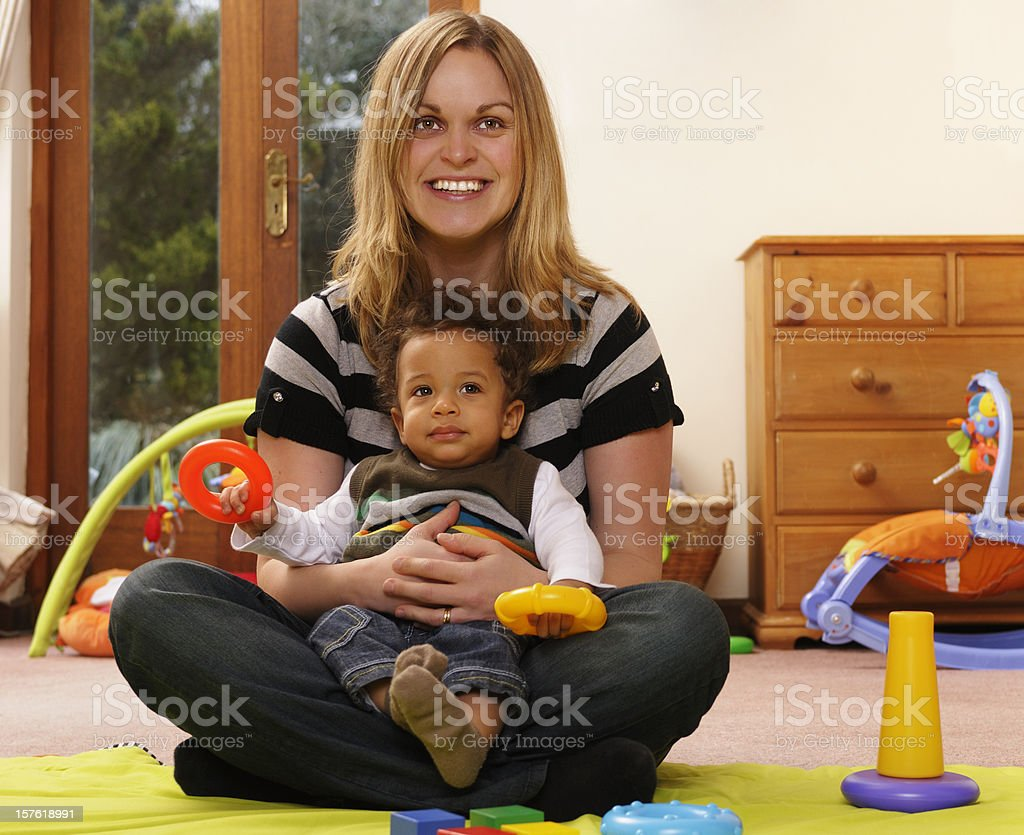 Baby Playing With Rings While Being Held By Carer stock photo