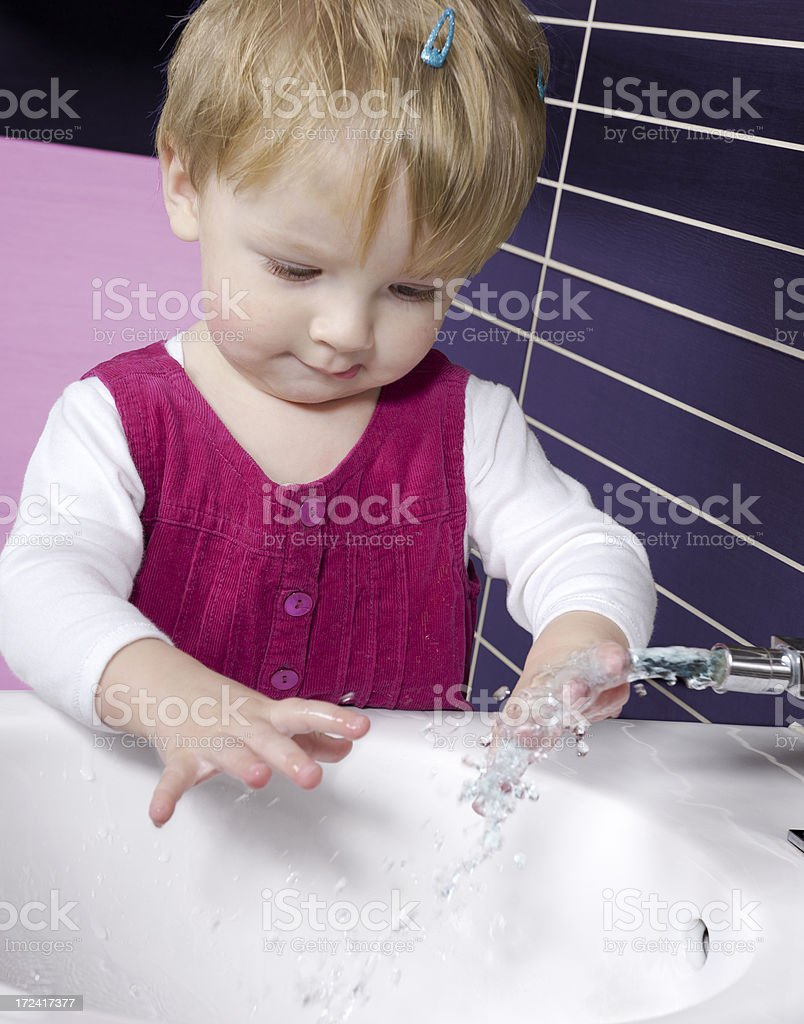 Baby plays water in the bathroom. royalty-free stock photo