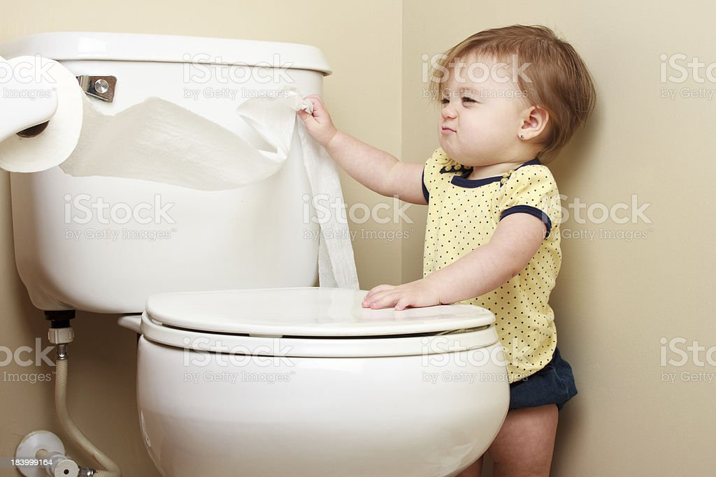 Baby pulling toilet paper off the roll stock photo