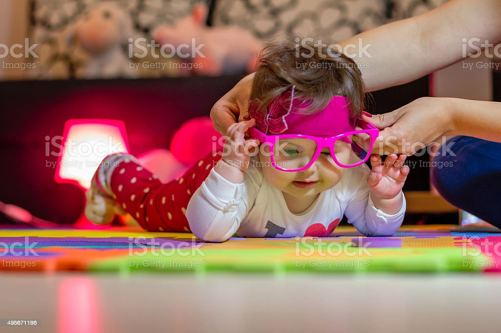 baby refuses to wear glasses stock photo