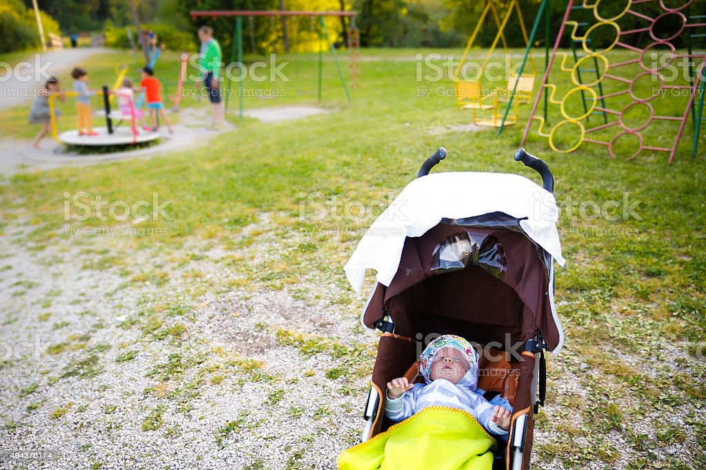 Baby resting in a stroller on playground stock photo